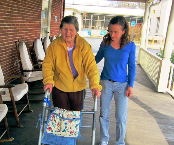 therapist helping elderly woman walk assisted