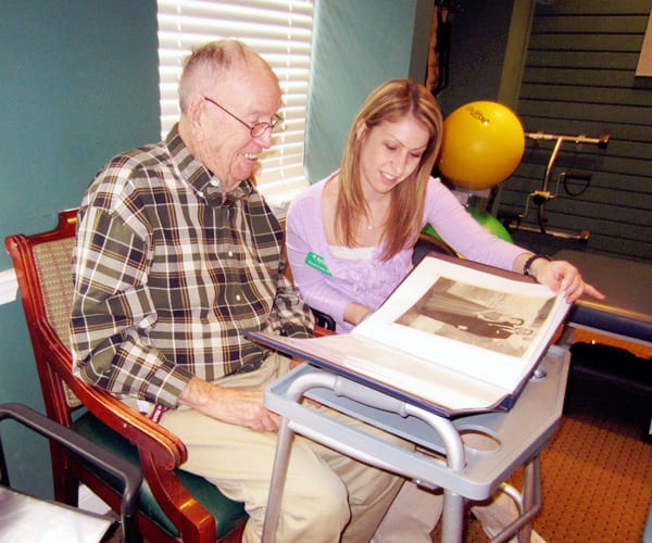 therapist and resident looking at scrapbook