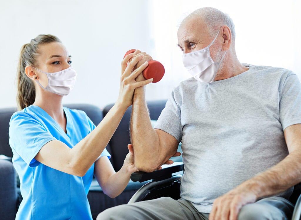 Doctor or nurse caregiver exercise with senior man, both wearing protective masks,  at home or nursing home